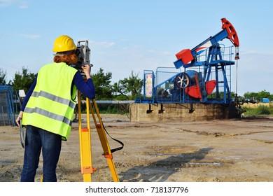 A woman engineer - land surveyor at work on an European oil well