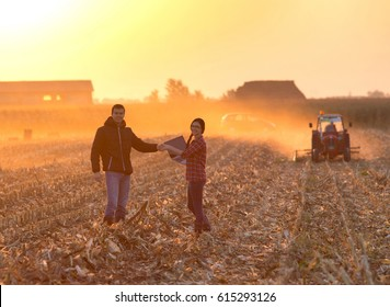 Woman engineer with laptop and landowner shaking hands on field at sunset with tractor working in background. Agribusiness concept