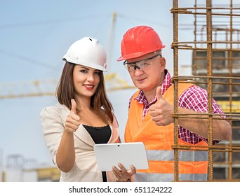 Woman engineer and male worker at construction site, wearing helmets and smart vest, thumbs up.