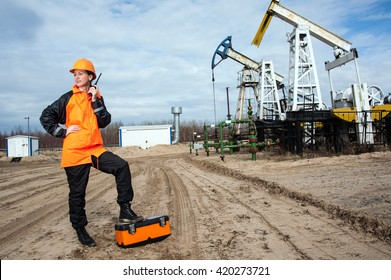 Woman engineer in the oil field talking on the radio wearing orange helmet and work clothes. Industrial site background.