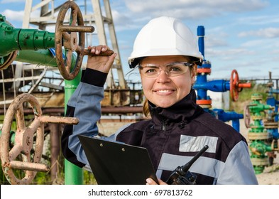 Woman engineer in the oilfield near wellhead wearing white helmet and work clothes. Industrial site background. Oil and gas concept.