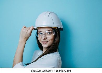 Woman engineer in white helmet and glasses, protective clothes., helmet and protective glasses.
