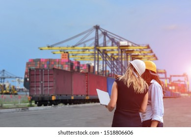 woman engineer worker inspect container with computer box on train platform in port cargo freight for import export shipping with crane bridge in harbor background