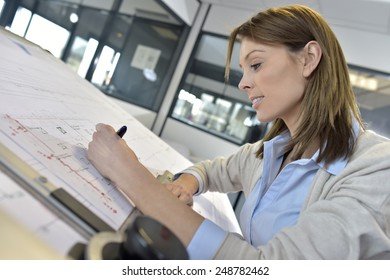 Woman engineer working on blueprint in office