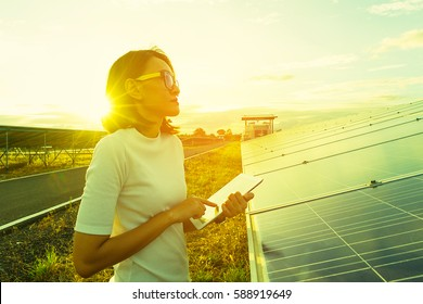 woman engineer working on checking checking status equipment at solar power plant with tablet checklist; woman working on outdoor at solar power plant