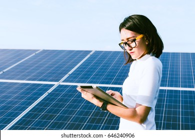 woman engineer working on checking checking status equipment at solar power plant with tablet checklist; woman working at solar power plant
