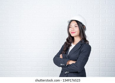 Woman of engineering holding a hat, Separate the white brick wall made gestures with sign language.
