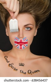 Woman with english flag on face and tea bag, black background