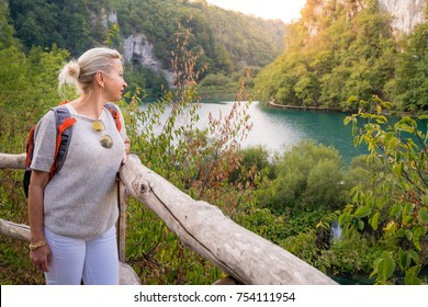Woman is enjoing the view at Plitvice Lakes National Park at sunset