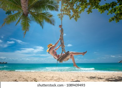 woman enjoy happy the nature of the sea beach by sitting on the wooden swing tie under the shadow of the plam tree, long weekend and vacation holidays spent slow life on the beach