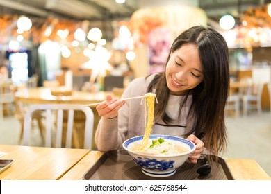 Woman enjoy her noodles in japanese restaurant