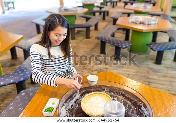 Woman enjoy japanese white noodles in restaurant