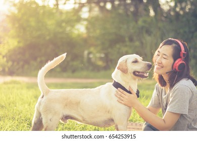 woman enjoy listening to music by headphone outdoor and playing with friendly dog at sunset