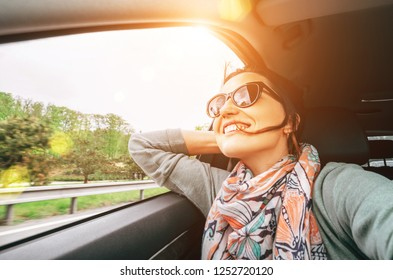 Woman enjoy with view from car window when traveling by auto selfie wide angle shot