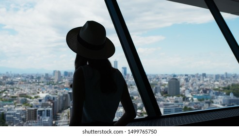 Woman enjoy the view of Tokyo city at observation deck