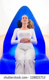 Woman enjoying alpha therapy in spa, colorful lights stimulating the psyche