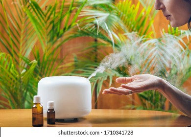 Woman Enjoying Aroma Therapy Steam Scent from Home Essential Oil Diffuser or Air Humidifier. Ultrasonic technology, increasing air humidity indoors for more comfortable living conditions - Shutterstock ID 1710341728