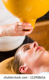 Woman enjoying a Ayurveda oil massage treatment in a spa