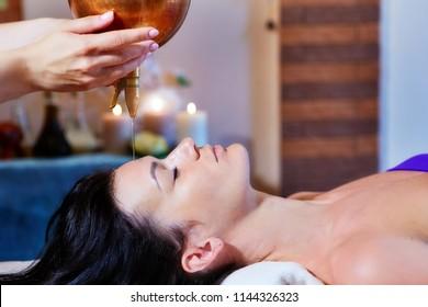 Woman enjoying a Ayurveda oil massage treatment in a spa.