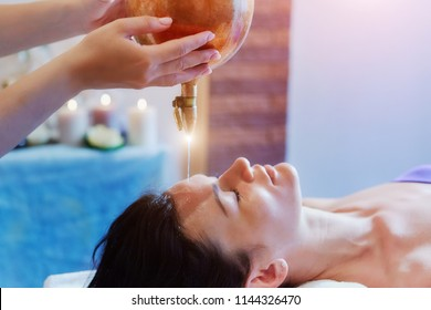 Woman enjoying a Ayurveda oil massage treatment in a spa.
