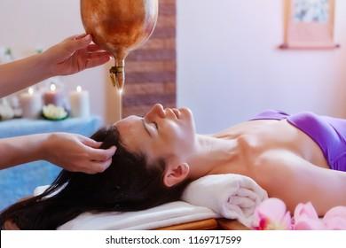 Woman enjoying a Ayurveda oil massage treatment in a spa