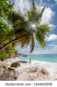 Woman enjoying the beach at Seychelles Praslin beach paradise holiday vacation. Travel to Seychelles for beautiful sea and white beaches in Indian Ocean, Africa. Rocks on the beach.