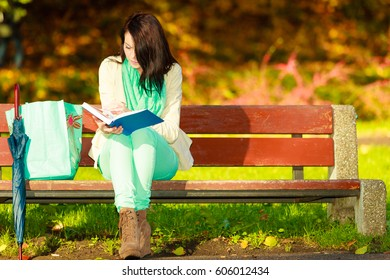 Woman enjoying beautiful autumn nature weather, reading book sitting on bench in park during sunny autumnal day,