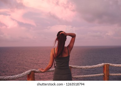Woman enjoying beautiful colorful sunset above sea from cape