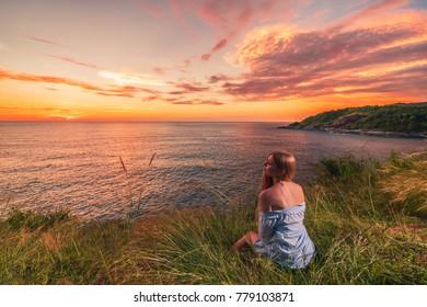 Woman enjoying beautiful colorful sunset above sea from cape.