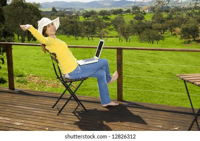 Woman enjoying a beautiful day with a laptop on her home-field