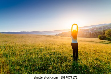 Woman enjoying beautiful sunrise at mountains. Freedom and relax concept