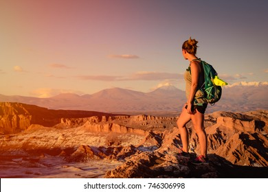 Woman enjoying the beautiful sunset in the Atacama desert in Chile, with views of the distant mountains & volcanoes