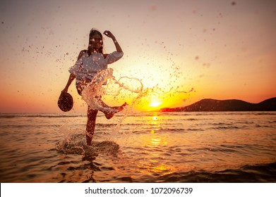 Woman Enjoying Beautiful Sunset on the Beach