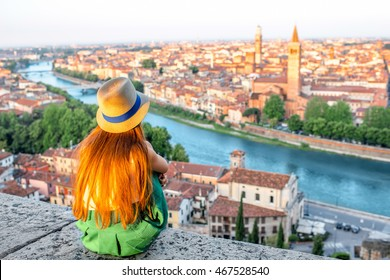 Woman enjoying beautiful view on Verona city in Italy on the sunrise. Verona is famous city of love in the north of Italy.
