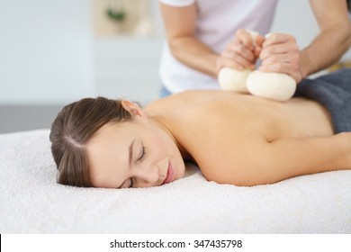 woman enjoying a beauty treatment with herbal compresses in a spa with eyes closed