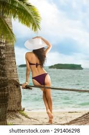 Woman enjoying blue sea. Vacation. Back view.