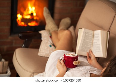 Woman enjoying a book and a hot chocolate drink by lying the fire on a sofa - focus on the cup and hand, shallow depth