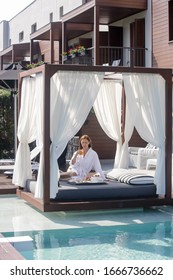 Woman enjoying breakfast in outdoor daybed with side curtains next to the swimming pool, the perfect begining of summer day