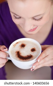 woman enjoying cappuccino with a smiley on foam