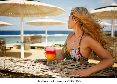 Woman enjoying a cocktail on the beach