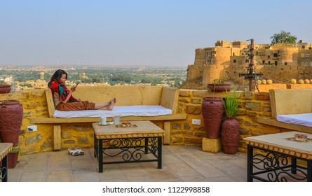 A woman enjoying at coffee shop of Jaisalmer Fort in Rajasthan, India.