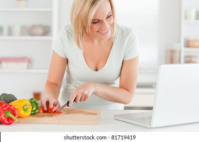 Woman enjoying cooking looking for a recipe on the laptop in the kitchen