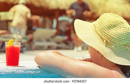 Woman enjoying drink on the edge of the swimming pool