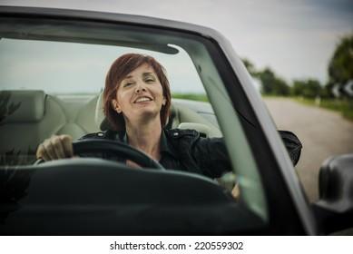 Woman enjoying driving her convertible car
