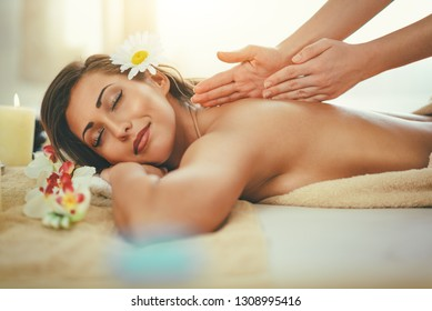 Woman enjoying during a back massage at a spa.
