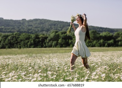 Woman enjoying a field of daisies, beautiful woman lying in a meadow of flowers, beautiful girl relaxing outdoors, having fun, holding plant, happy young lady and spring-green nature, harmony concept.