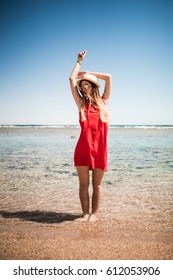 Woman enjoying freedom on a ocean shore with hands raised