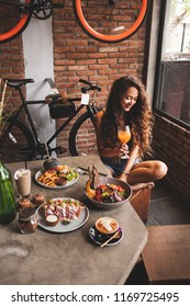 Woman enjoying fresh organic vegetarian food and glass of kombucha in hipster style cafe with bicycle design