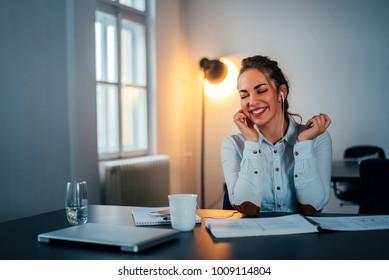 Woman enjoying good music at modern office interior.
