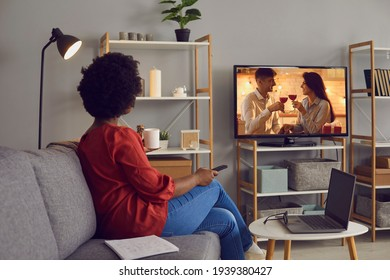 Woman enjoying good romcom serial in the evening. Single African American lady sitting alone at home, drinking coffee and watching romantic love story on soap opera entertainment TV channel, back view